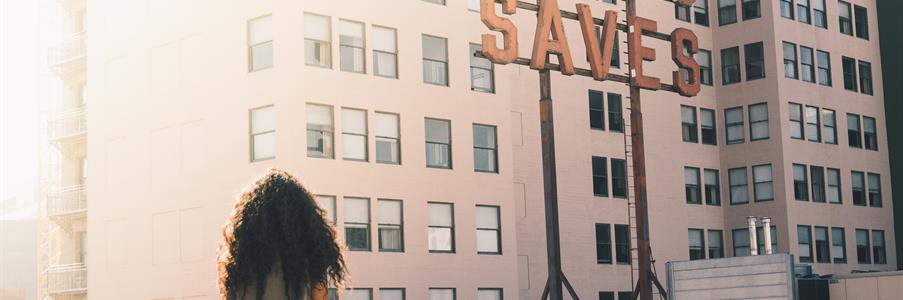 Girl sits on a rooftop, facing a large sign that reads JESUS SAVES