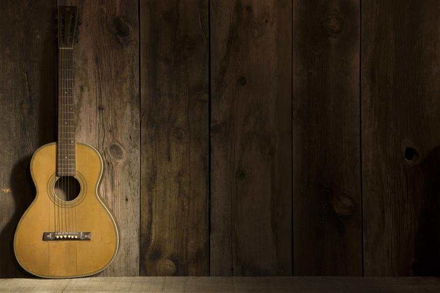 an acoustic guitar sitting against a wall.