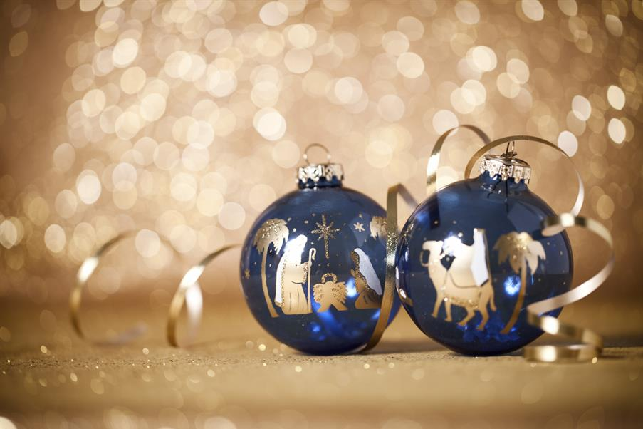 istock image of two christmas baubles decorated with nativity images - Mary and Joseph praying over baby Jesus; a Wise Man riding on a camel.